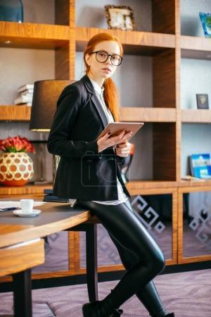 female wear glasses work on digital tablet during break