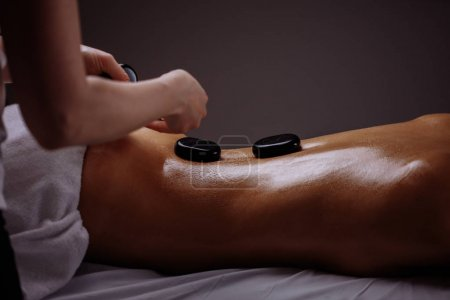 woman getting hot stone massage in spa salon. Beauty treatment concept