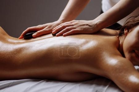 young Woman getting hot stone massage at spa salon