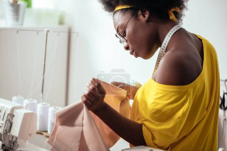 african woman seamstress looking at pink fabrics and standing in workshop