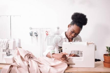 woman seamstress sitting and sews on sewing machine. Dressmaker working