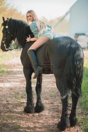 brunette woman riding dark horse at summer green forest.