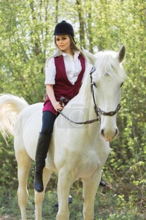 brunette woman riding dark horse at summer green forest.
