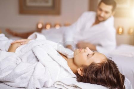 Photo pour Homme et femme couchée sur massage lits au centre de spa et de bien-être de luxe asiatique - image libre de droit