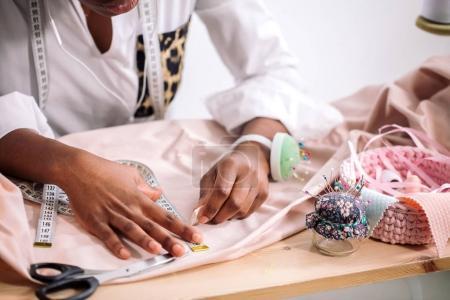 Photo pour Couturière africaine travaillant avec du tissu rose prend des mesures - image libre de droit