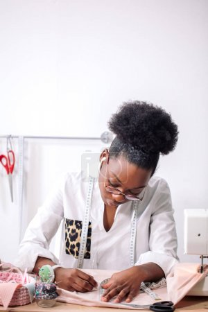 african seamstress working with fabric takes measures