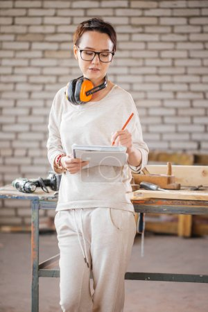 hardworking professional female worker with pen and tablet in workshop