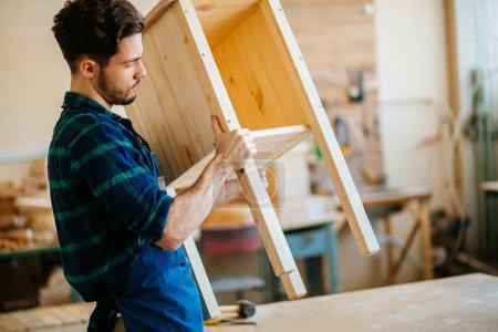 carpenter testing wood plank evenness at workshop