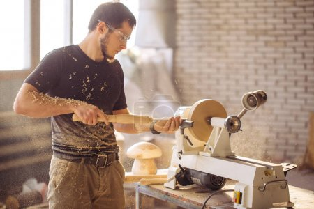 man working at small wood lathe, an artisan carves piece of wood
