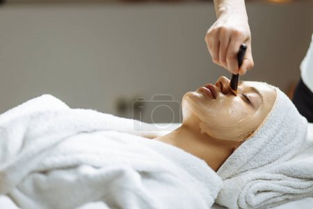 Spa concept. Young woman with clay facial mask in beauty salon, close up