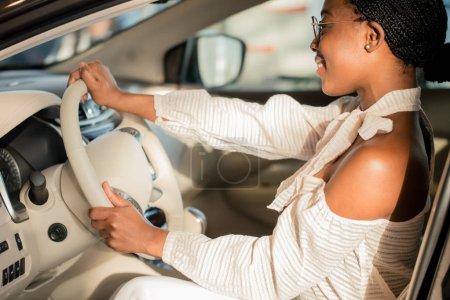 cheerful african female driver inside car
