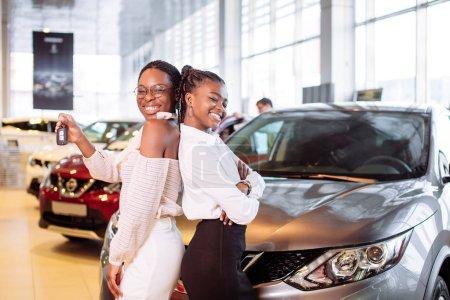 Photo pour Jeune femme heureuse deux afro-américaine près de la voiture avec les clés à la main concept d'achat de voiture - image libre de droit