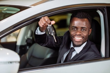 Photo for Happy african vehicle buyer inside his new car with car key - Royalty Free Image