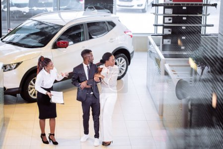 car salesman standing at dealership telling about features of car to customers