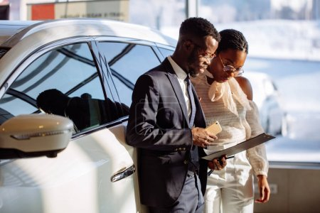 Car dealer showing vehicle to black woman