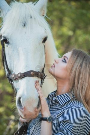 beautiful girl stroking horse outside
