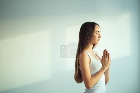 woman practicing yoga and meditation, holding palms together in namaste mudra