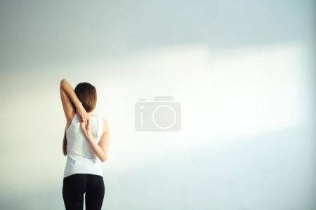 Rear view of fit woman doing gomukhasana in yoga class