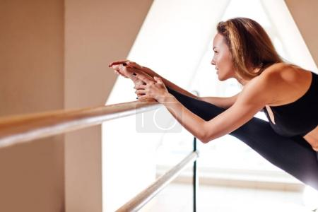 Girl smiling and looking in mirror while stretching body in fitness class