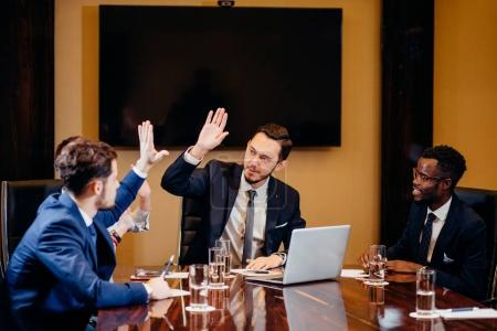 business team giving high fives gesture as they laugh and cheer their success
