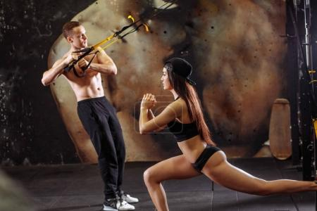 Photo for Young sporty couple workout in gym with elastic trx equipment - Royalty Free Image