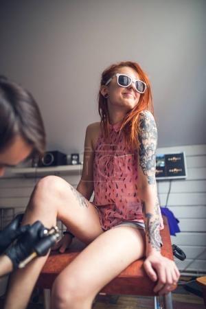 A tattoo artist makes a tattoo pretty girl