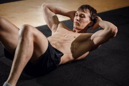 guy making exercise, sit-ups and cross crunches for abs muscles