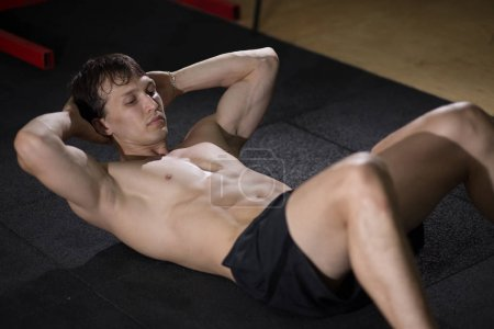 Muscular man exercising doing sit up exercise. Athlete with six pack