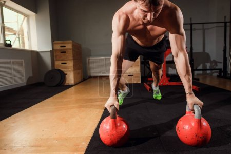 Photo for Gym man push-up strength pushup exercise with Kettlebell in a workout - Royalty Free Image