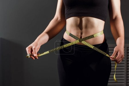 close up of slimming woman body with measure tape