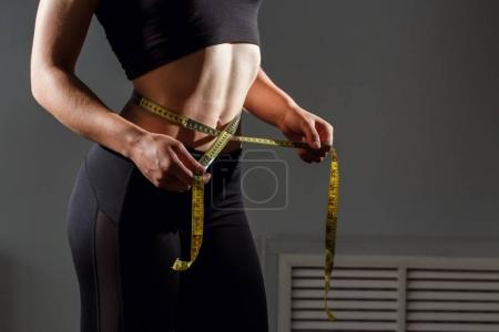 Woman measuring her waistline. Closeup female with perfect slim body and torso