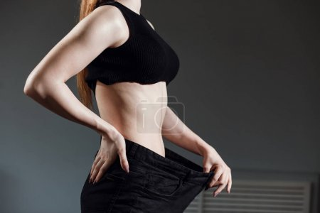 Slim Woman with healthy thin body,showing her old jeans after successful diet.