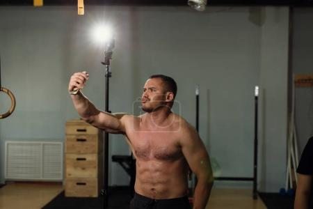 Handsome shirtless muscular bodybuilder man taking selfie with cell phone