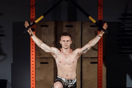Photo for TRX training. Cross fit instructor at the gym doing TRX Excersise. Fitness man workout on the rings. Fitness man in the gym. Fitness style. Workout on rings. Sport and fitness - Royalty Free Image