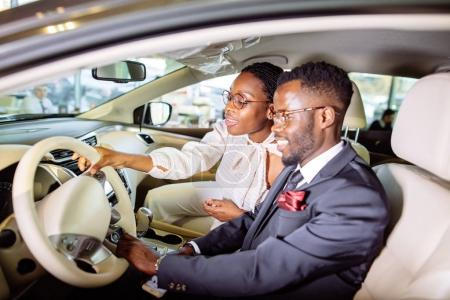 beautiful african couple is choosing new car at dealership.
