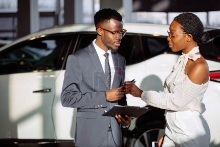 Car dealer showing vehicle to black woman