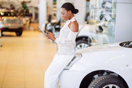 Professional female salesperson working in car dealership