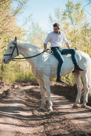 man in a shirt riding on a brown horse