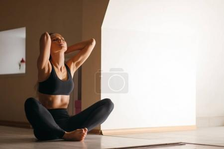 woman doing yoga exercise, sitting in baddha konasana, butterfly pose