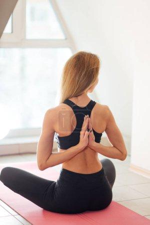 woman doing yoga in reverse prayer pose. Pashchima Namaskarasana