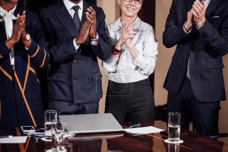 multiracial business team applauding in meeting room