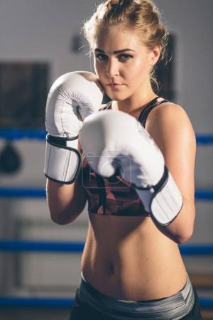 Female Boxer wearing gloves posing in boxing studio