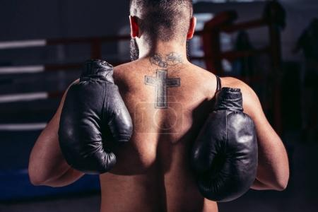 guy back towards camera, pair of boxing gloves over his shoulder
