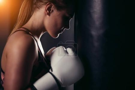 Photo for Sexy fighter girl in gym with boxing bag. Long hair woman fitness model resting after boxing - Royalty Free Image