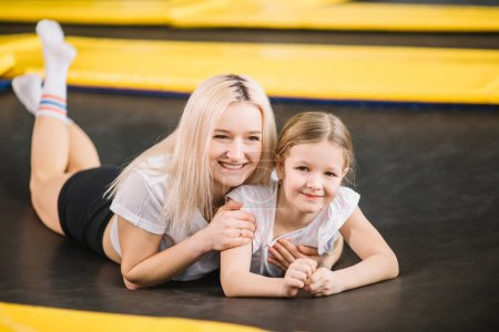 mother and little girl playing at playground and lying on a trampoline