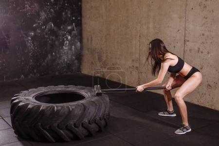 woman smashing large tire with sledgehammer during intense workout in fit gym