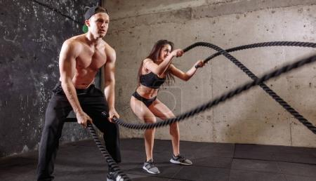 Photo for Woman and man training together doing battling rope workout - Royalty Free Image