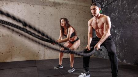 Photo for Couple doing cardio exercise with battle ropes at gym - Royalty Free Image