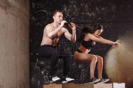 man and woman jumping on fit box