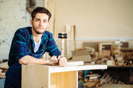 carpenter hammering a nail into wooden board